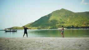 Ragazzo e ragazza che giocano sulla spiaggia contro lo sfondo delle montagne stock footage