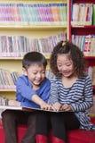 Ragazzo e ragazza che leggono insieme Immagine Stock