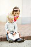 Ragazzo e ragazza che leggono un libro fotografia stock libera da diritti