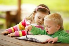 Ragazzo e ragazza che leggono un libro fotografia stock