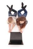 Ragazzo e ragazza che per mezzo di un computer portatile che si trova sul pavimento Fotografia Stock Libera da Diritti