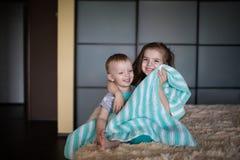 Ragazzo e ragazza che si nascondono sotto la coperta Immagini Stock Libere da Diritti