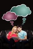 Ragazzo e ragazza che si siedono insieme ad un pc della compressa e che guardano un Mo Immagine Stock Libera da Diritti