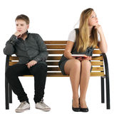 Ragazzo e ragazza che si siedono su un banco Fotografia Stock