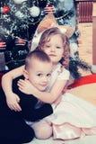 Ragazzo e ragazza con i regali vicino all'albero di Natale Immagini Stock Libere da Diritti
