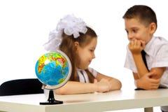 Ragazzo e ragazza con il globo Fotografia Stock