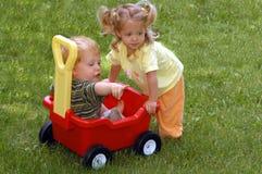 Ragazzo e ragazza con il vagone fotografia stock libera da diritti