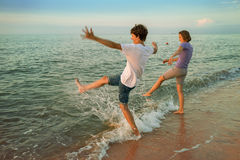 Ragazzo e ragazza divertendosi le onde spruzzate del mare Immagini Stock