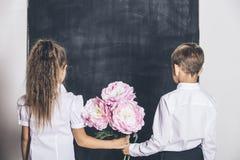Ragazzo e ragazza felici dalla scuola elementare con i fiori in loro Immagini Stock Libere da Diritti