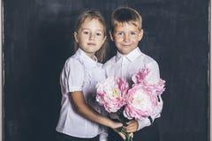 Ragazzo e ragazza felici dalla scuola elementare con i fiori in loro Fotografia Stock