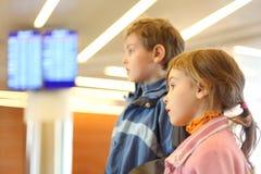Ragazzo e ragazza in schermi dell'aeroporto su priorità bassa Immagine Stock
