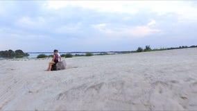 Ragazzo e ragazza sulla banca del fiume - esaminare la distanza video d archivio