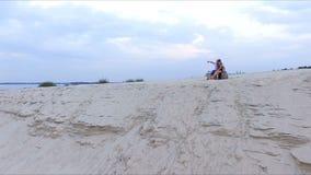 Ragazzo e ragazza sulla banca del fiume - esaminare la distanza stock footage