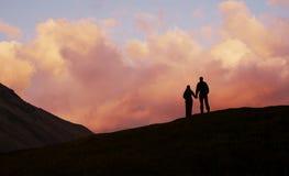 Ragazzo e ragazza sulla priorità bassa di tramonto fotografia stock