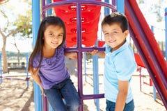 Ragazzo e ragazza sulla struttura di scalata in parco Immagini Stock