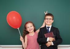 Ragazzo e ragazza vicino al consiglio scolastico Fotografie Stock