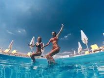 Ragazzo e ragazze che si siedono sullo scrittorio praticante il surfing e sullo sguardo sul mare blu Fotografia Stock