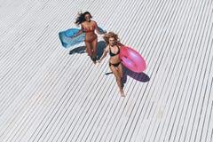 Ragazzo e ragazze che si siedono sullo scrittorio praticante il surfing e sullo sguardo sul mare blu Fotografia Stock Libera da Diritti