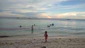 Ragazzo e ragazze che si siedono sullo scrittorio praticante il surfing e sullo sguardo sul mare blu immagini stock