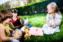 Ragazzo e ragazze con i giocattoli su erba fotografie stock