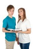 Ragazzo e una ragazza con un libro aperto Fotografie Stock