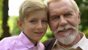 Ragazzo e uomo anziano che posano per la macchina fotografica, sorridendo, fidandosi delle relazioni con il nonno archivi video