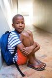 Ragazzo elementare che si siede sul corridoio a scuola Immagine Stock Libera da Diritti
