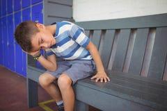Ragazzo elementare premuroso che si siede sul banco Immagine Stock