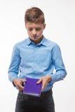 Ragazzo emozionale castana in una camicia blu con un diario e una penna a disposizione Fotografie Stock Libere da Diritti