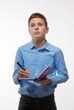 Ragazzo emozionale castana in una camicia blu con un diario e una penna a disposizione Immagini Stock Libere da Diritti