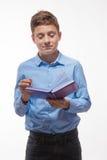Ragazzo emozionale castana in una camicia blu con un diario e una penna a disposizione Immagine Stock
