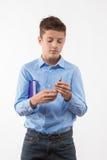 Ragazzo emozionale dell'adolescente castana in una camicia blu con un diario e una penna a disposizione Immagini Stock