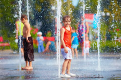 Ragazzo emozionante divertendosi fra i getti di acqua, in fontana Estate I Fotografie Stock Libere da Diritti
