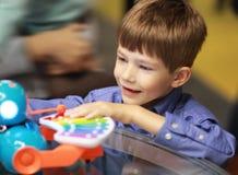 Ragazzo emozionante felice in un centro commerciale del grande magazzino/che collauda i giocattoli interattivi e che sceglie un r Immagine Stock Libera da Diritti