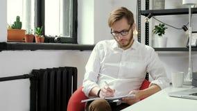 Ragazzo europeo bello che lavora al progetto alla scrivania moderna 20s 4k stock footage