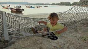 Ragazzo felice in amaca sulla spiaggia video d archivio