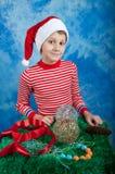 Ragazzo felice in cappello di Santa su fondo blu Fotografia Stock
