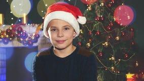 Ragazzo felice in cappello di Santa vicino all'albero di Natale decorato archivi video
