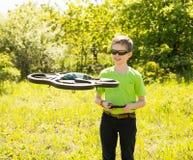 Ragazzo felice che gioca con il fuco di volo con la macchina fotografica controllata da MP fotografia stock