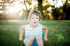 Ragazzo felice che gioca con l'automobile del giocattolo e della palla su erba verde immagine stock