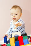 Ragazzo felice che gioca la costruzione del blocco per grafici. Fotografia Stock