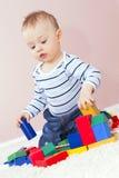 Ragazzo felice che gioca la costruzione del blocco per grafici. Fotografie Stock Libere da Diritti