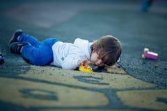 Ragazzo felice che gioca nel parco con sporcizia da un foro del vaso immagine stock