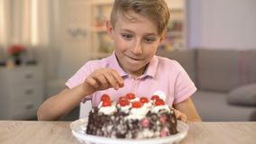 Ragazzo felice che mangia ciliegia dalla cima del dolce crema, dessert dolce, spuntino di infanzia archivi video
