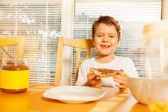 Ragazzo felice che mangia pane tostato con la diffusione del cioccolato immagine stock
