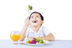 Ragazzo felice con insalata su bianco Fotografia Stock