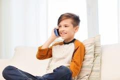 Ragazzo felice che rivolge allo smartphone a casa Fotografia Stock