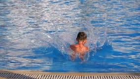 Ragazzo felice che salta nello stagno di acqua blu Movimento lento archivi video