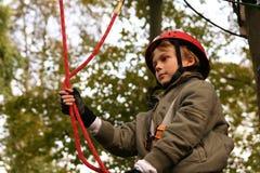 Ragazzo felice che scala nel parco di avventura Fotografia Stock