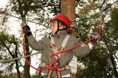 Ragazzo felice che scala nel parco di avventura Immagini Stock Libere da Diritti